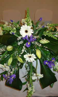 Top table arrangement containing ivory gerbera, antirrhinum, spirea and blue iris