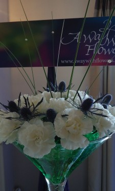 Martini vase with white carnations, eryngium and steel grass arranged in green crystal gel