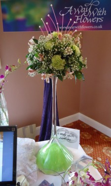 Green carnations and pink alstromeria arranged on upturned martini vase