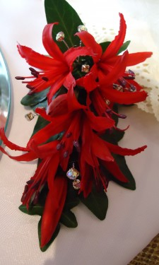 Red nerine corsage with iridescent crystal