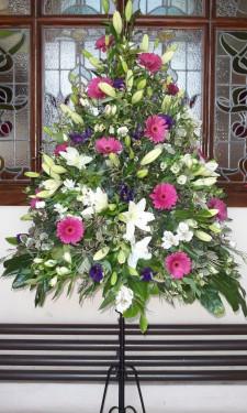 Porch arrangement with pink gerbera, ivory lilies, alstromeria, and purple lizianthus