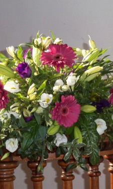 Small low arrangement with pink gerbera, ivory lilies and lizianthus and purple lizianthus