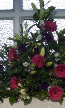 Window arrangement with pink gerbera, ivory lilies, lizianthus & purple lizianthus