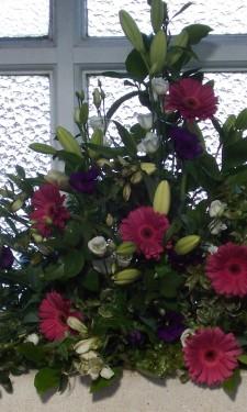 Window arrangement with pink gerbera, ivory lilies, lizianthus & purple lizianthus