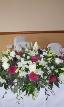 Top table arrangement of ivory lily, lizianthus, pink gerbera and purple lizianthus