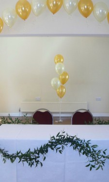 Gold and Ivory balloon arch with soft ruscus table garland