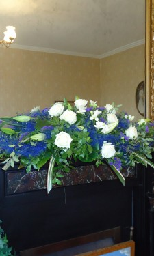 Mantelpiece arrangement with lily , rose, freesia, statice and blue sisal
