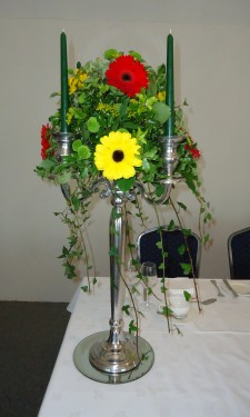 Candelabra arrangement with red and yellow gerbera and green spray chrysanthemum