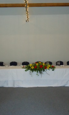 Top table setting with central arrangement and candelabra at Crug Glas