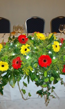 Top table arrangement of red and yellow gerbera, lily, solidago and lights