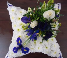 White based pillow wreath with blue iris ivory rose and freesia