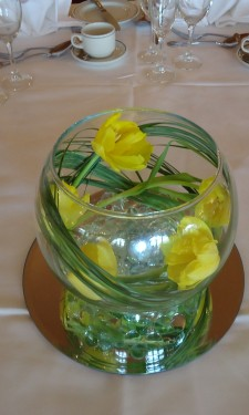 Double yellow tulips in a goldfish bowl with bear grass, clear nuggets, light & mirror tile