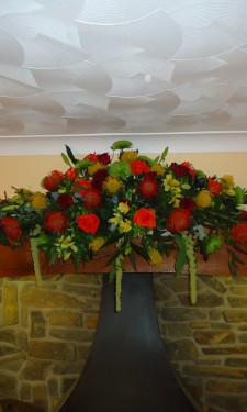 Mixed autumn colours provided by proteas, roses, chrysanthemum and alstromeria and trailing amaranthus