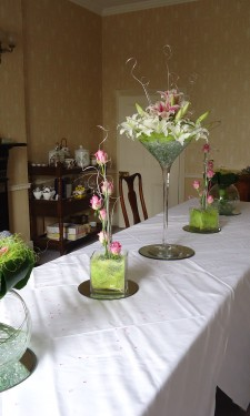 Variety of table centres with arrangements in a martini vase, tank vase and goldfish bowl
