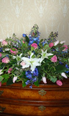 Long low arrangement of ivory lily pink rose and blue larkspur