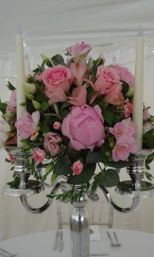Round arrangement of peony, roses, spray roses and freesia on candelabra