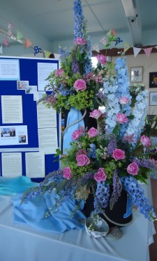 Pink roses, blue delphiniums, antirrhinums,buddleia and alchemilla mollis.