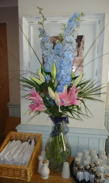 pink lilies and blue delphiniums with steel grass and palm leaves