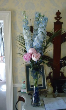 Pink peonies, blue delphiniums and phoenix palm leaves at reception area