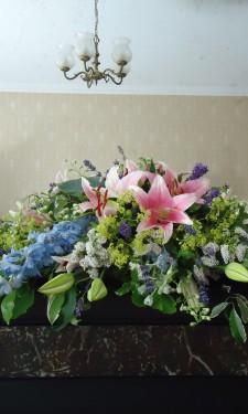 Mantelpiece arrangement with lily , delphinium, veronica, alchemilla mollis and lavendar