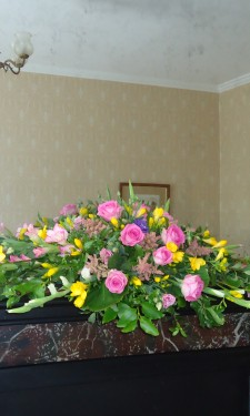 Mantelpiece arrangement with roses, gladiolus, astilbe, and freesia