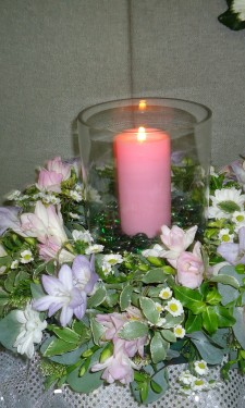 Hurricane vase with candle surrounded by pink and lilac & white wreath ring