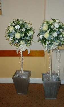 Ivory topiary trees trimmed with ribbon