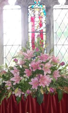 Altar arrangement of pink lily, roses and bridal gladiolus
