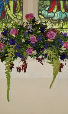 Window arrangement with pink roses, hydrangea and purple lizianthus and trailing amaranthus