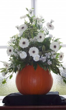Ivory gerbera, alstromeria, and carnations arranged in a pumkin