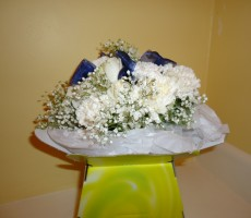 Ivory roses, carnations and gypsophila with navy organza ribbon inserts