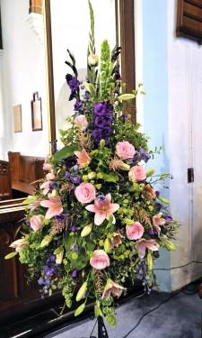 Large pedestal arrangement with pink lilies, esperance roses, purple lizianthus, astilbe & delphinium