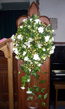 Pew end with white alstromeria, spray carnations and peach hypericum berries