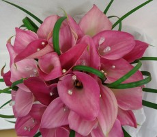 Hand tied of pink calla lilies with bear grass loops and iridescent crystal