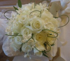 Hand tied bouquet of roses and stephanotis with pearls and flexi grass loops