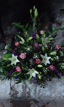 Triangular arrangement of lilies, roses bouvardia, lizianthus and solomon's seal