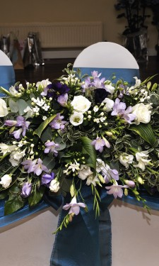 Top table arrangement containing ivory freesia, lizianthus, bouvardia & roses and purple/ lilac freesia and lizianthus
