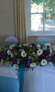 Top table arrangement containing ivory gerbera, yellow alstromeria, pink spray carnations and lilac freesia.