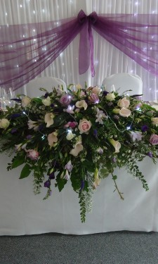 Top table arrangement containing roses, calla lilies, lizianthus, freesia, aster, mixed foliage and lights