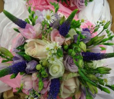 Hand-tied bouquet containing ivory, pink, & lilac roses, purple lizianthus, & veronica, and ivory freesia & white aster