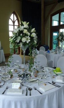 Oriental lilies, roses, carnations, freesia and trailing ivy in martini vases